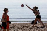 Una mujer con mascarilla para el coronavirus pasea por la playa en Barcelona.