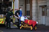 Dos trabajadores del King's College Hospital de Londres trasladan a un enfermo