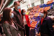 Los Reyes, junto a la ministra de Industria, durante su visita a Mercamadrid.