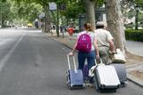 Dos turistas pasean con su maleta por el Paseo del Prado