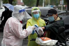 Voluntarios toman la temperatura a un hombre en el distrito de Chuanying en Jilin