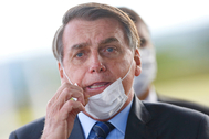 FILE PHOTO: FILE PHOTO: Brazil's President Jair lt;HIT gt;Bolsonaro lt;/HIT gt; adjusts his mask as he leaves Alvorada Palace, amid the coronavirus disease (COVID-19) outbreak in Brasilia