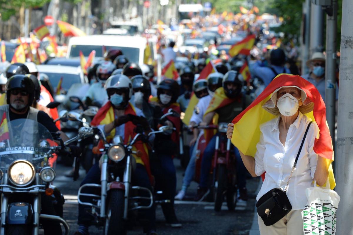 Una mujer se cubre del sol con una bandera de España, en la manifestación organizada este sábado por Vox, en Madrid.