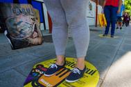 Varias personas esperan su turno para recoger una bolsa de comida de la ONG del chef José Andrés en Madrid.