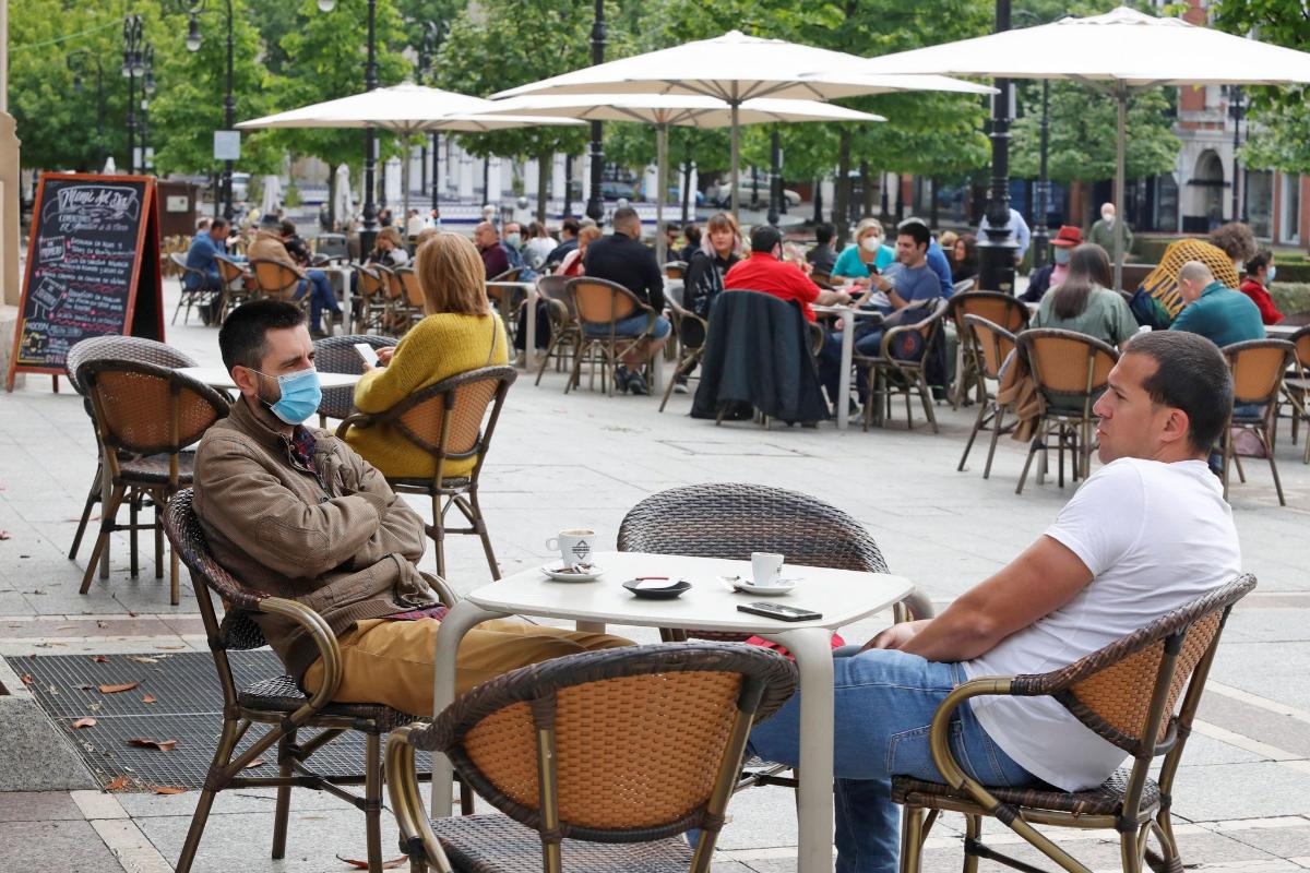 Dos ciudadanos, este sábado, en una terraza del Paseo de Begoña, en Gijón.