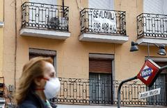 Una mujer camina delante de un piso en alquiler en Madrid, durante la cuarentena.
