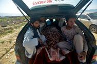 Un grupo de afganos llevan en su coche una víctima de un atentado reciente de los talibán.