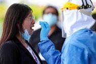 Un sanitario realiza una prueba de Covid-19 a una mujer.