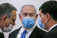 Benjamin Netanyahu habla con sus abogados en la primera jornada del juicio.