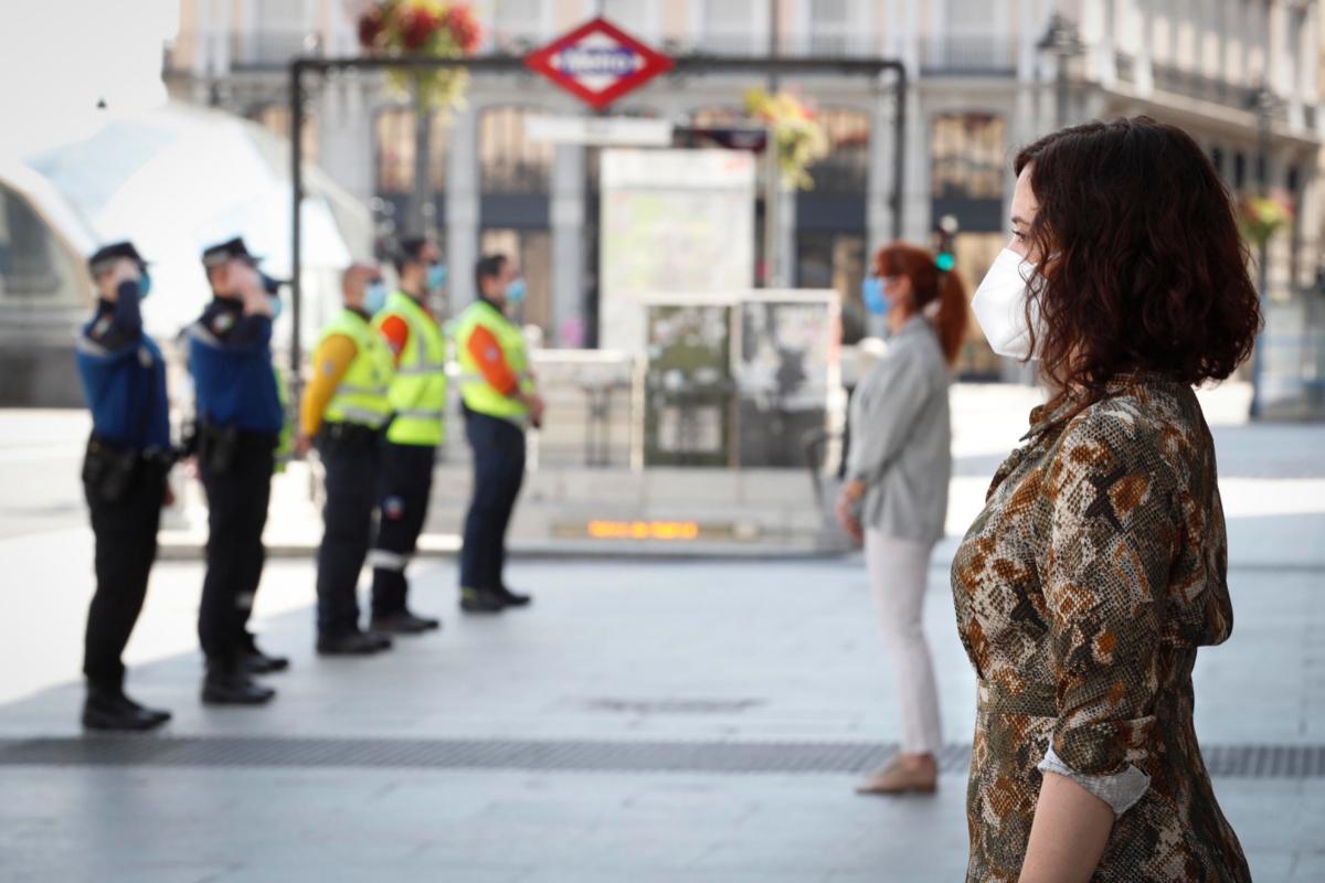 La presidenta madrileña, Isabel Díaz Ayuso, guarda un minuto de silencio por los fallecidos del coronavirus, este domingo, en Madrid.