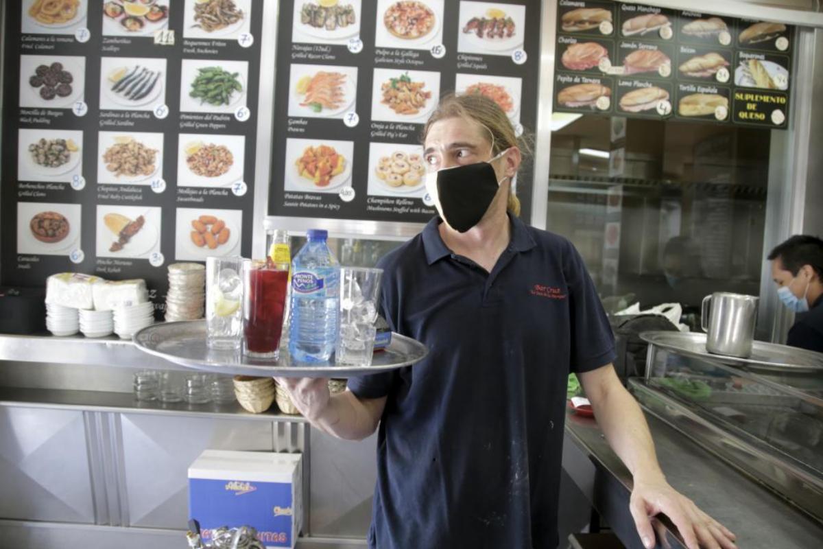 Raúl carga su bandeja en la barra del local
