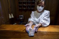 Una empleada del hotel Nava Real de Navacerrada muestra las llaves precintadas en plástico tras una mampara.