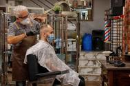 Un peluquero con un cliente en una barbería de Reus.