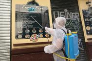 Un empleado desinfecta los carteles de un restaurante de Málaga.