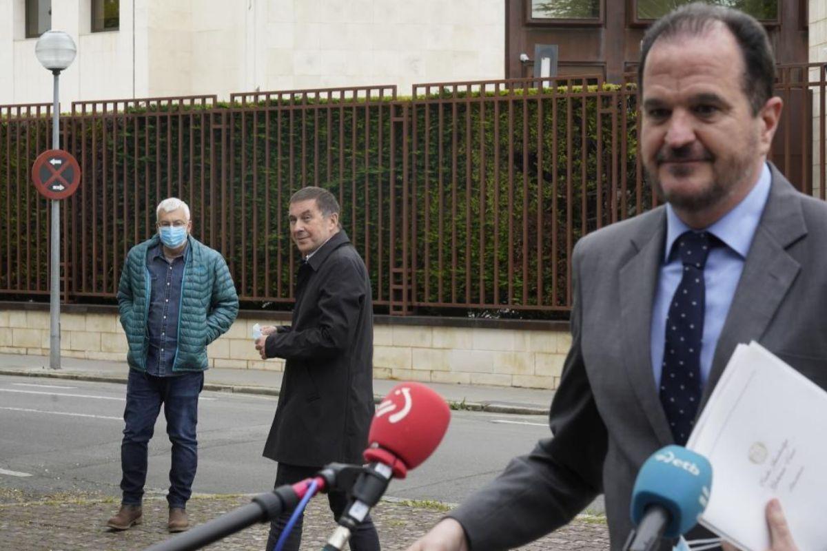 Carlos Iturgaiz atiende a los medios de comunicación mientras es observado por Arnaldo Otegi.