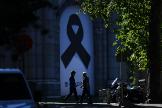 Paseantes con mascarilla pasan ante el lazo negro instalado en la plaza de Cibeles de Madrid en recuerdo de los muertos por coronavirus.