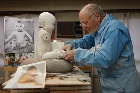 Antonio López en su estudio moldea un bebé de escayola, autorretrato escultórico a partir de una foto suya de niño.