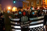 Un manifestante muestra una pancarta durante las protestas por la muerte de George Floyd, ayer en Minneapolis.