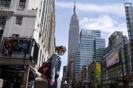 Una mujer pasea con mascarilla por Nueva York.