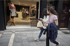 Dos jóvenes pasan por la puerta de una tienda de ropa en la jornada en la que Navarra inicia la Fase 2 de la desescalada.