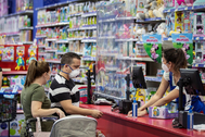 Clientes con mascarillas en el interior de una tienda del centro comercial Lagoh en Sevilla, reabierto en la fase 2 de la desescalada.