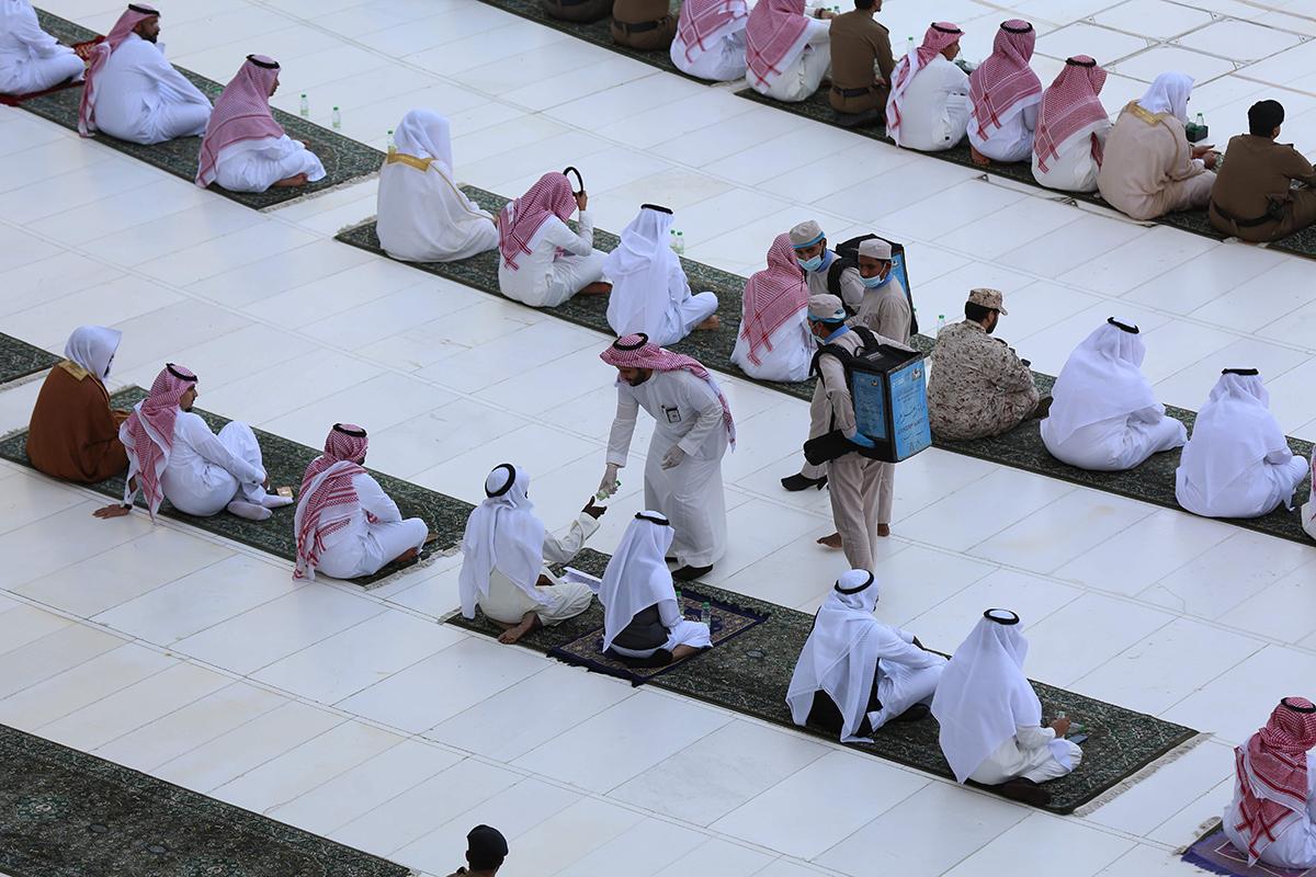 Voluntarios dan agua a los devotos que rezan en La Meca.