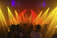 Cientos de personas disfrutan en la pista de baile de una discoteca.
