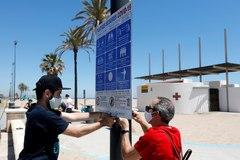 Instalación de carteles informativos en la playa de La Malvarrosa de Valencia.