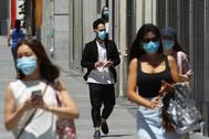 Varias personas caminan provistas de mascarillas por Madrid.