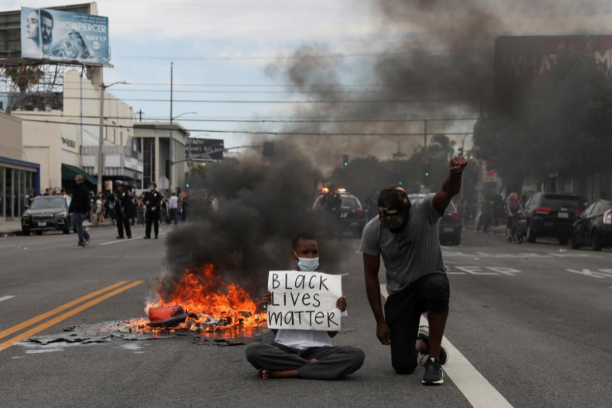 Dos hombres protestan contra la Policía en Los Angeles.