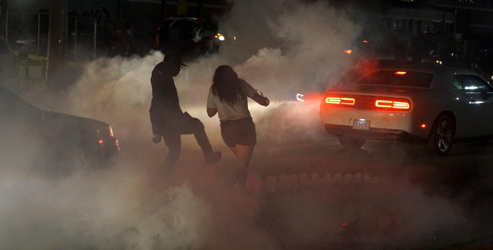 Un hombre aleja de una mujer un bote de gas lacrimógeno durante una protesta contra la muerte del afroamericano George Floyd en Minnesota.