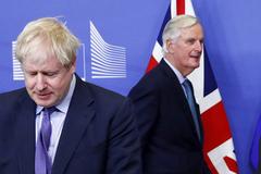 Michel Barnier pasa junto a Boris Johnson.