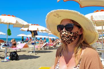 Una mujer se protege con una mascarilla en una playa recién abierta