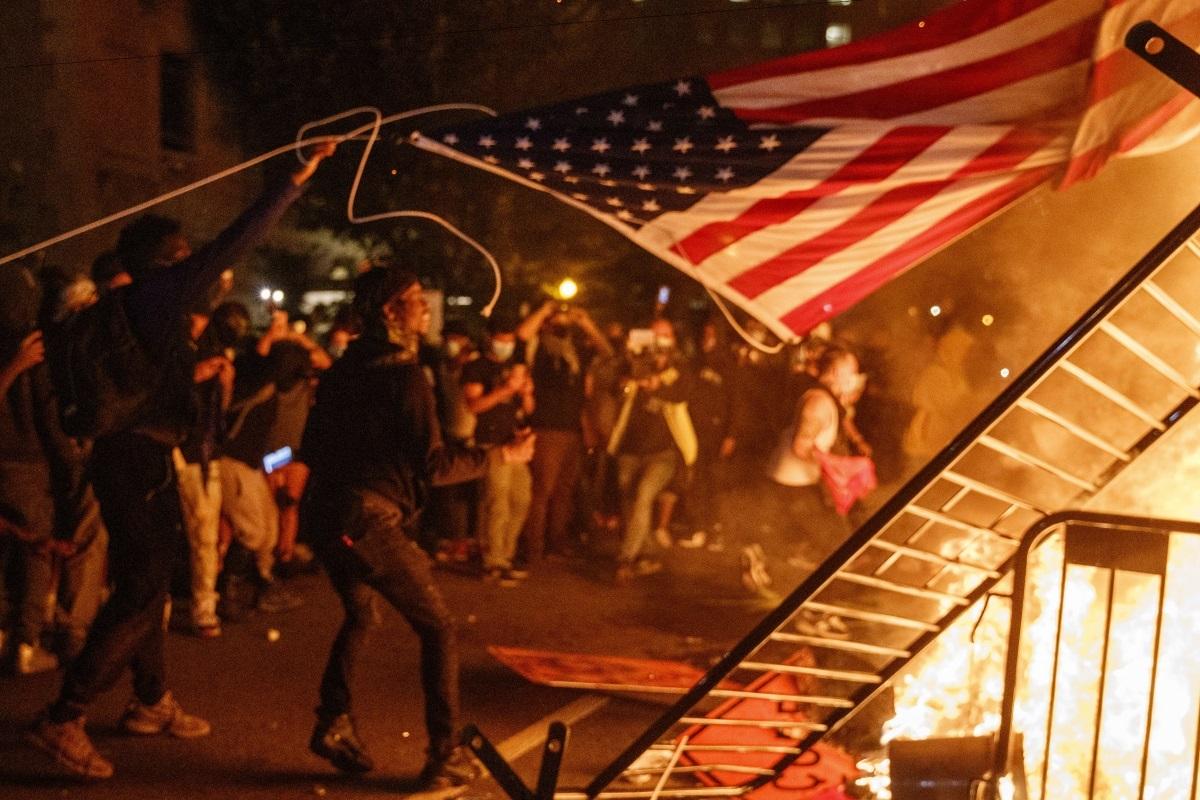 Los manifestantes queman una bandera de EEUU a las puertas de la Casa Blanca.
