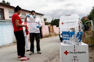 Miembros de la Cruz Roja reparten alimentos en la Cañada Real