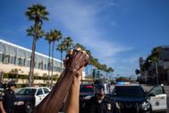Un hombre blanco y una mujer negra agarran sus manos, durante una protesta por la muerte de George Floyd.