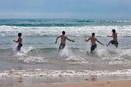 Un gupo de jóvenes entra al agua en Gandía.