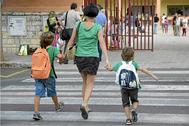 Una madre lleva a sus hijos al colegio, en una imagen de archivo, en Palma.