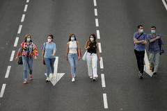 Varias personas con mascarilla caminan por el Paseo de la Castellana, en Madrid.