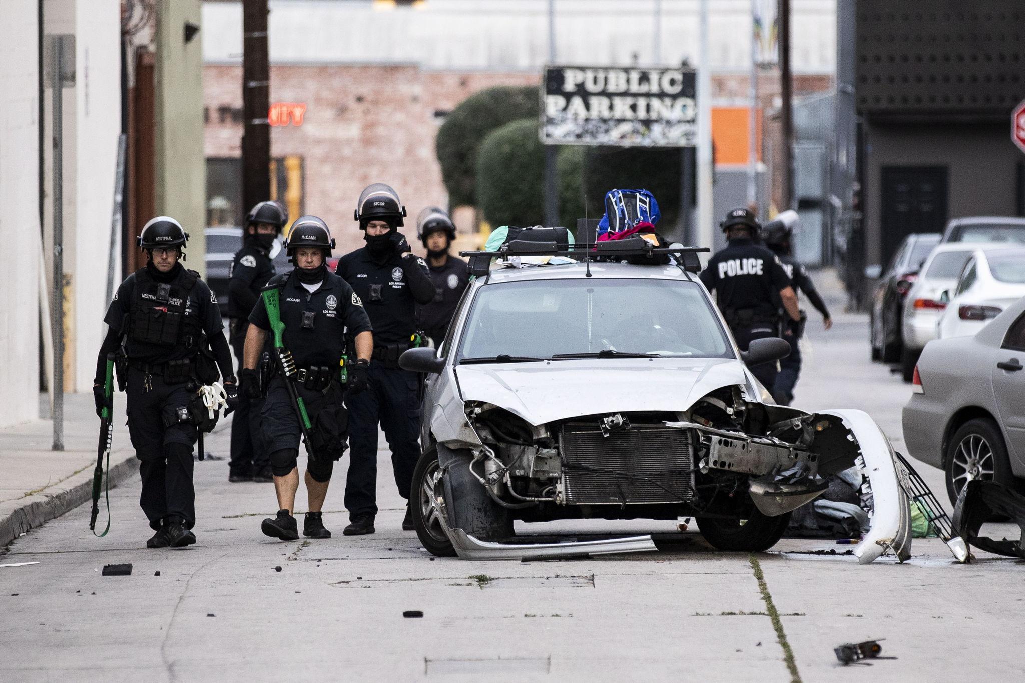 Varios policías avanzan por las calles de Hollywood, California, entre vehículos quemados en la noche del lunes.