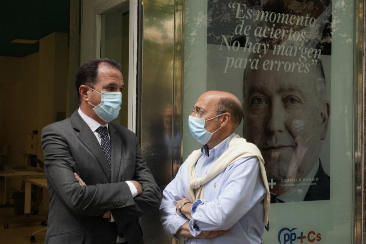 Carlos Iturgaiz conversa con su compañero Carlos Urquijo en la oficina electoral del PP vasco en Vitoria.