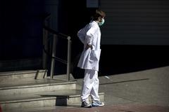 Un profesional sanitario descansa a la puerta de las Urgencias del Hospital Ramon y Cajal de Madrid.