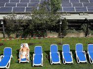 Un hombre toma el sol junto a placas solares de una azotea en Berlín./