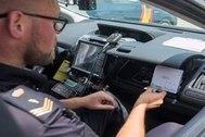 Un oficial de la Policía Nacional comprueba la identidad de un ciudadano desde un vehículo conectado.