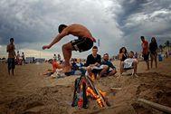 Un joven salta una hoguera en la playa de la Malva-rosa de Valencia.
