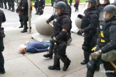 La línea policial avanza sin prestar atención al hombre que yace inconsciente en el suelo.