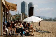 Varias personas en un chiringuito en la playa de Barcelona.