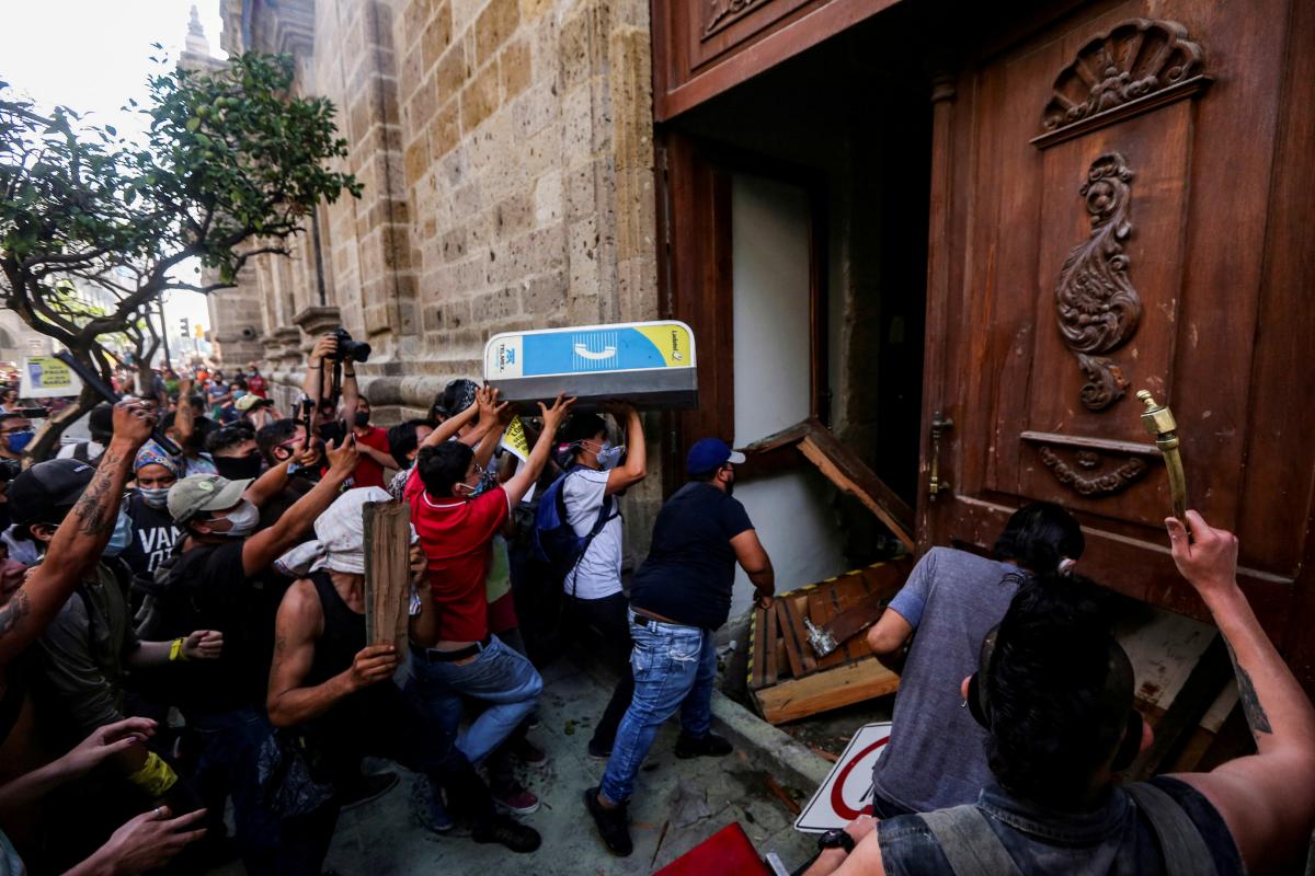 Manifestantes tiran abajo una puerta del Palacio de Gobierno del Estado de Jalisco, en Guadalajara.