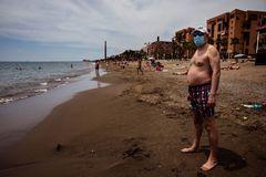 Un hombre con mascarilla en la arena de la Misericordia de Málaga.