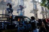 Manifestantes brincan y destruyen una patrulla que arde tras ser quemada durante una protesta en Guadalajara.